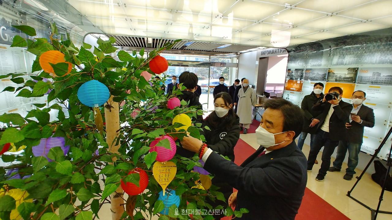 윤성이 총장과 학생 대표들이 희망나무에 소원등을 달고 있다.