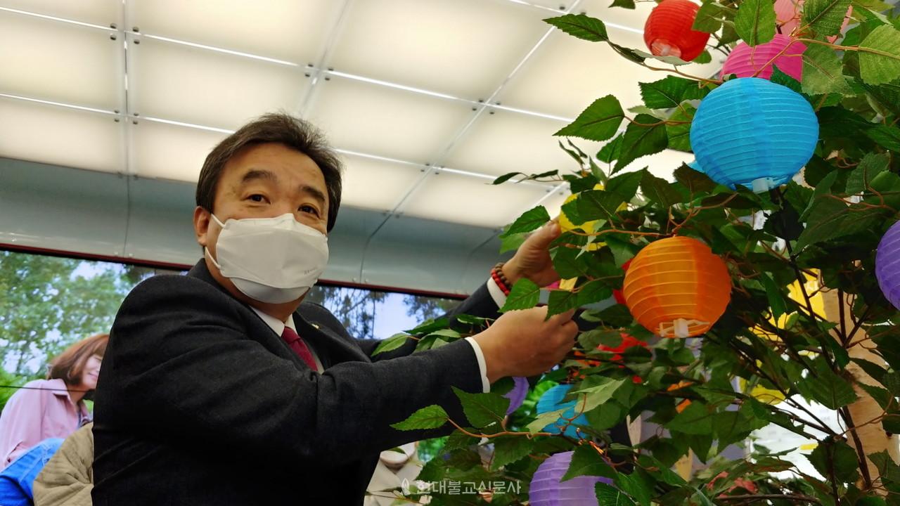 윤성이 총장이 희망나무에 소원등을 달고 있다.