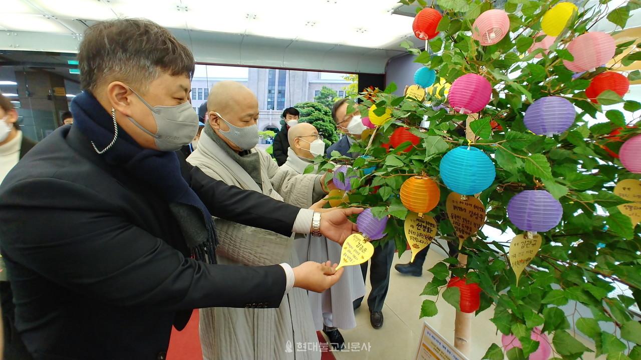 기획부총장 종호 스님 등이 희망나무에 소원등을 달고 있다.